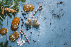 Christmas background with gingerbread, candy cane, hearts and fir tree. Royalty Free Stock Images