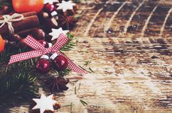 Christmas background with gingerbread cookie stars, fir tree twigs. Red balls, spices and fresh tangerines on wooden boards Stock Images