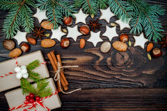 Christmas background with gingerbread cookies, fir branches and presents in boxes on the old wooden board. Copy space. Stock Image