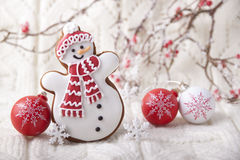 Christmas background with gingerbread in the form a snowman. On a white knit fabric Stock Photo