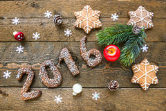 Christmas background with gingerbread numbers 2016, fir branches and decorations on the old wooden board. Christmas background with gingerbread numbers 2016 on Royalty Free Stock Photography
