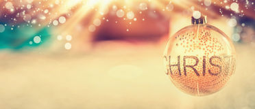 Christmas background with glass decorating  ball and text Christmas at blurred room and bokeh. Lighting, banner Royalty Free Stock Images