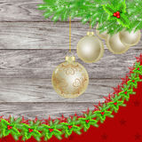Christmas background with golden bauble. S, fir tree and holly garland over wooden background Stock Images