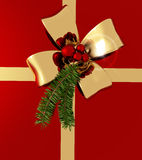 Christmas background. Golden bow with sprig of fir tree on red background Stock Photo