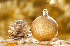 Christmas background with golden christmas ball and cone Royalty Free Stock Images