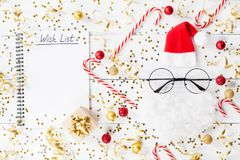 Christmas background of golden confetti, gift or present boxes, wish list notebook and funny Santa on table top view. Flat lay. Christmas background of golden stock photos