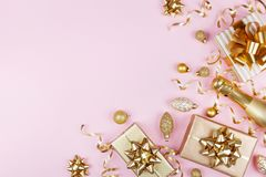 Christmas background with golden gift or present box, champagne and holiday decorations on pink pastel table top view. Flat lay. royalty free stock photography