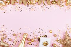 Christmas background with golden gift or present box, champagne and holiday decorations on pink pastel table top view. Flat lay. stock photos