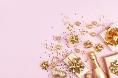 Christmas background with golden gift or present box, champagne and holiday decorations on pink pastel table top view. Flat lay. royalty free stock photos