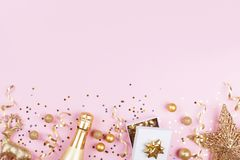 Christmas background with golden gift or present box, champagne and holiday decorations on pink pastel table top view. Flat lay. royalty free stock image