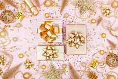 Christmas background with golden gift or present box, champagne and holiday decorations on pink pastel table top view. Flat lay. Christmas background with golden stock images