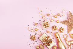 Christmas background with golden gift or present box, champagne and holiday decorations on pink pastel table top view. Flat lay. Christmas background with golden royalty free stock image