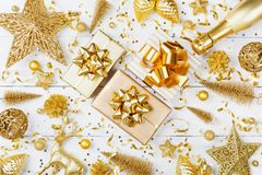 Christmas background with golden gift or present box, champagne and holiday decorations on white table top view. Greeting card. Flat lay style stock photos