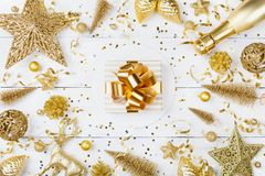 Christmas background with golden gift or present box, champagne and holiday decorations on white table top view. Greeting card. Flat lay style royalty free stock photos