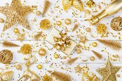 Christmas background with golden gift or present box, champagne and holiday decorations on white table top view. Flat lay. Christmas background with golden gift royalty free stock photos