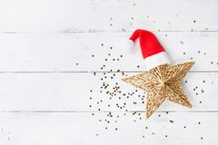 Christmas background of golden star with Santa hat and confetti top view. Flat lay. stock image