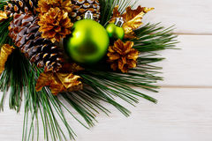 Christmas background with green ornaments and golden pine cones Stock Images