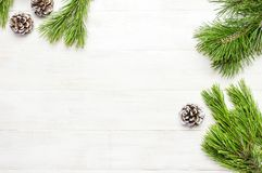 Christmas background, green pine branches, cones decorated with snow on white wooden table. Creative composition with border and c stock image