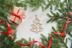 Christmas background. Green tree branches frame on white wooden background, gift box with red satin ribbon, handmade wooden Christ stock image