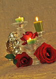 Christmas Background/greeting card. 3 red roses 3 candles and a praying angle on a gold silky background Stock Image