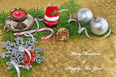 Christmas background greeting card with baubles, gift, fir and decorations over golden background Stock Image