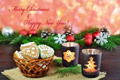 Christmas background, greeting card with burning candle and gingerbread cookies Stock Images