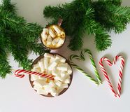 Christmas background, greeting card with a Cup of coffee or chocolate with marshmallows, lollipops, a red plate and tree branches. Christmas background, greeting Royalty Free Stock Image