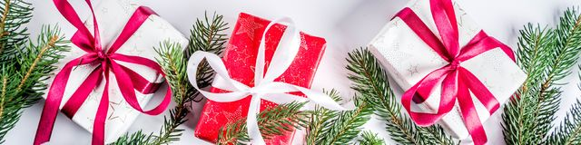 Christmas background with gifts boxes. Christmas background for greeting card, with Christmas tree branches, decoration and gifts boxes with ribbons, on white Stock Image