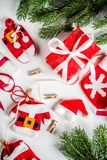 Christmas background with gifts boxes. Christmas background for greeting card, with Christmas tree branches, decoration and gifts boxes with ribbons, on white Royalty Free Stock Images