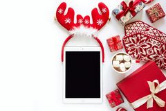 Christmas background with handmade presents wrapped in craft paper, cup of hot chocolate and tablet. Flat lay. Space for copy stock photos