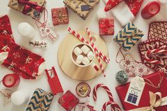 Christmas background with handmade presents wrapped in craft paper and woman`s hand with cup of hot chocolate Stock Photography