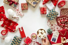 Christmas background with handmade presents wrapped in craft paper and woman`s hand with cup of hot chocolate Royalty Free Stock Photo