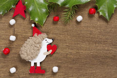 Christmas background with hedgehog and Holly leaves Stock Image