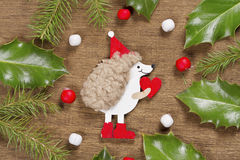 Christmas background with hedgehog and Holly leaves Stock Photo