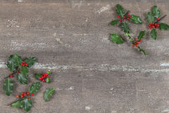 Christmas background with Holly leaves and berries on a brown wooden . Royalty Free Stock Images