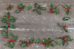 Christmas background with Holly leaves and berries on a brown wooden . Royalty Free Stock Image