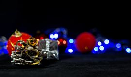 Christmas background image, red balls on the blurred background, blue lights, focus on the pine cone stock photography