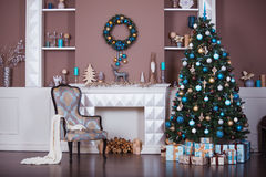 Christmas background. Interior room decorated in xmas style. No people. New year tree and fireplace Royalty Free Stock Photography