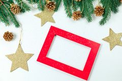 Christmas background. Christmas jewelry on fir-tree branches, gold spheres, garlands and a red frame for a photo or an inscriptio. New Year`s background stock image