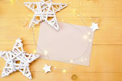 Christmas background kraft sheet of paper with place for your text and white christmas star and garland on a gold wooden Royalty Free Stock Image
