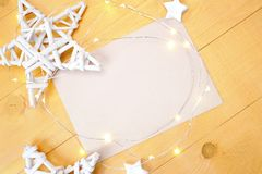 Christmas background kraft sheet of paper with place for your text and white christmas star and garland on a gold wooden Stock Images