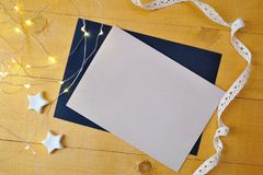 Christmas background kraft sheet of paper with place for your text and white christmas star and garland on a gold wooden Stock Photos