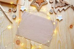 Christmas background kraft sheet of paper with place for your text and white christmas star and garland on wooden Stock Photos