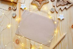 Christmas background kraft sheet of paper with place for your text and white christmas star and garland on wooden. Background. Flat lay, top view photo mockup Royalty Free Stock Images
