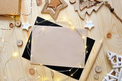 Christmas background kraft sheet of paper with place for your text and white christmas star and garland on wooden. Background. Flat lay, top view photo mockup Royalty Free Stock Photos