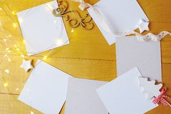 Christmas background kraft sheets of paper with place for your text and white christmas stars and garland on a gold Royalty Free Stock Images