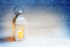 Christmas background with a lantern and burning candle light on Stock Images