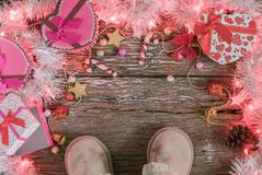 Christmas background, light and gift box with child boots. On old wood background, Xmas and New year concept Stock Images