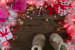 Christmas background, light and gift box with child boots. On old wood background, Xmas and New year concept Stock Photography