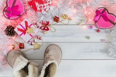 Christmas background, light and gift box with child boots Royalty Free Stock Image
